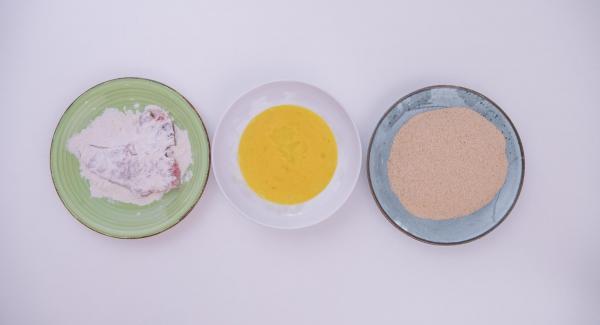 Impanare le costolette passandole prima nella farina, poi nelle uova sbattute e infine nel pangrattato.