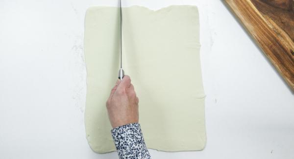 Distendere la pasta sfoglia sul piano di lavoro infarinato e tagliarla in dodici quadrati di circa 10 x 10 cm.