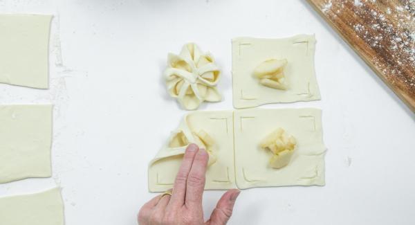 Collocare alcuni cubetti di pera al centro di ogni quadrato e ripiegare i bordi verso il centro, applicando infine una leggera pressione come mostrato in foto.