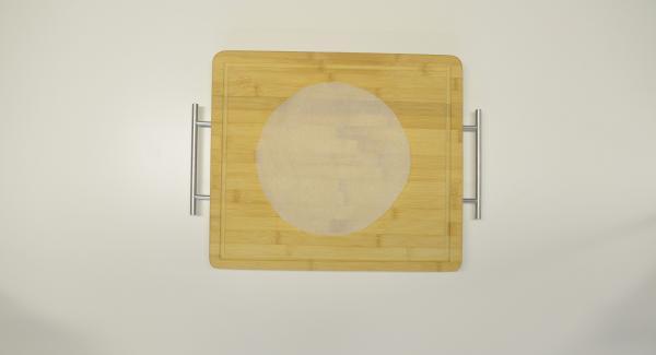 Con l'aiuto di un coperchio da 24 cm, tagliare un disco di carta da forno.