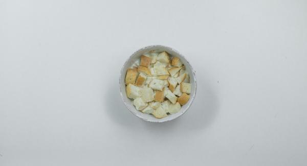 Tagliare a pezzettini il panino e immergerlo nel latte caldo.