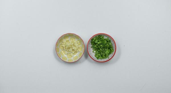 Pelare l'aglio e tagliarlo a dadini e tritare finemente le foglie di prezzemolo.