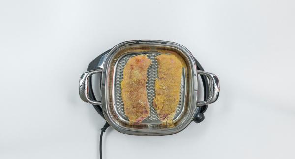 Versare in un piatto l'olio di semi di girasole. Passare nell'olio entrambi i lati delle cotolette impanate, far sgocciolare bene e posizionare la carne all'interno dell'Unità Arondo 28 cm.