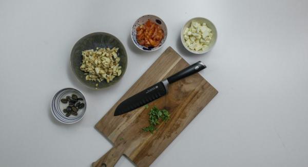 Tagliare il ripieno precedentemente conservato a pezzetti e cospargerlo di succo di limone. Pulire e tagliare a dadini il pomodoro. Tagliare nello stesso modo anche la feta e le olive. Tritare il tutto insieme alle foglie di basilico.