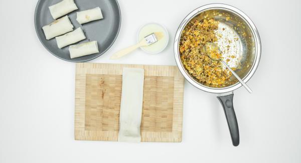 Stendere un foglio di pasta fillo sulla superficie di lavoro. Spennellare velocemente i bordi con l'albume, mettere un cucchiaio di ripieno e arrotolare velocemente fino a formare l'involtino.