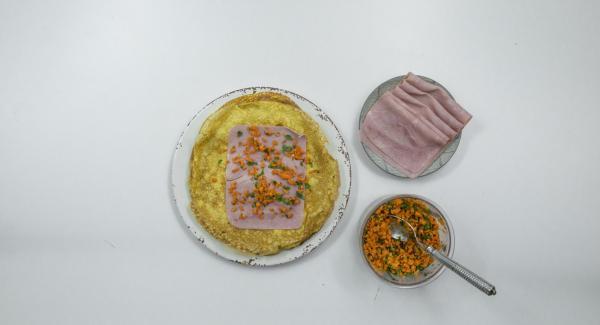 Disporre una fetta di prosciutto su ciascuna crêpe, spalmarvi sopra un cucchiaio del composto di carote e arrotolare ben stretto.