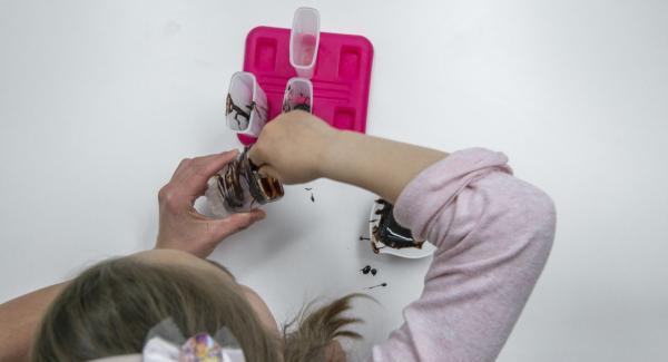 Sciogliere la salsa al cioccolato seguendo le istruzioni riportate sulla confezione e versarla negli stampi per ghiaccioli. Mentre si rassoda, scuotere gli stampi di tanto in tanto, in modo che il cioccolato si sparga bene sui bordi degli stampi.