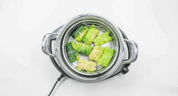 Versare dell'acqua (ca. 150 ml) nell'Unità di  cottura 24 cm 3,5 l e inserire la Softiera con gli involtini di verza. Coprire l'Unità con EasyQuick e posizionarla su Navigenio.