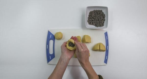 Dividere l'impasto in otto pezzi, riempire ciascuno con un cucchiaio di gocce di cioccolato, arrotolare e formare un panino.