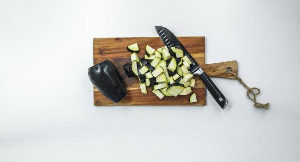 Pelare gli scalogni e l'aglio, tritarli finemente con Tritamix e metterli nell'Unità Gourmet. Mondare le melanzane e tagliarle a cubetti.
