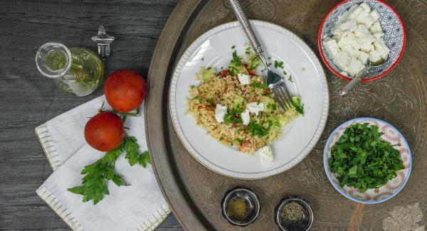 Spezzettare la feta grossolanamente. Tritare le foglie di prezzemolo. Versare la feta sopra l'insalata e cospargere il tutto con il prezzemolo.