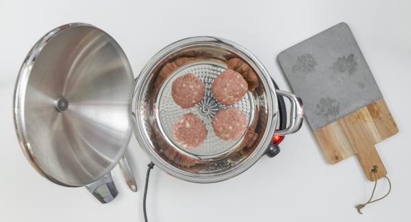 Al suono di Audiotherm, abbassare il calore, inserire gli hamburger nell'Unità e coprire nuovamente con il coperchio.