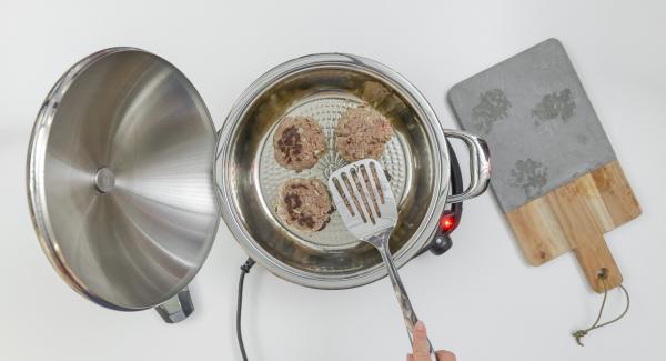 """Proseguire la cottura fino al raggiungimento del """"punto di girata"""" di 90°C, girare gli hamburger, chiudere l'Unità con il coperchio e lasciar completare la cottura a fuoco spento per ca. 8 minuti."""