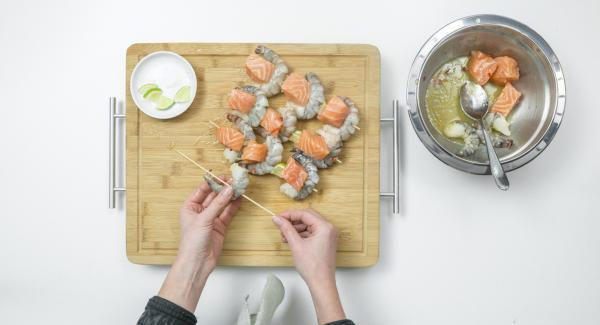 Sgocciolare i dadini di salmone e i gamberetti, infilarli su quattro spiedini, alternandoli, e aggiungendo due quarti di lime su ciascuno.