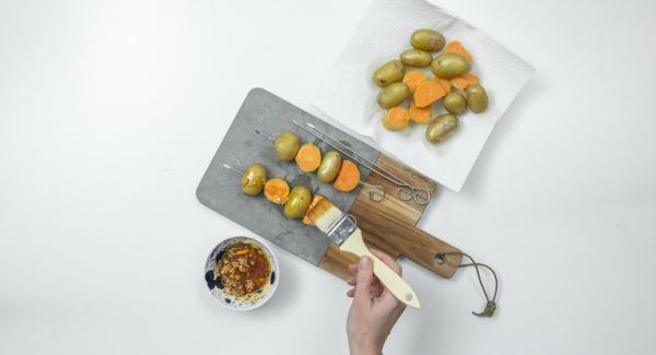 Infilare su degli spiedini le patate e i pezzi di patata dolce, alternandoli tra loro. Spennellarli leggermente con l'olio aromatizzato.