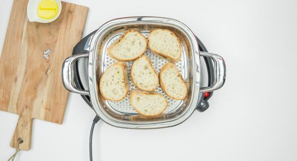 Al suono di Audiotherm, abbassare Navigenio a livello 2, inserire la metà delle fette di pane all'interno dell'Unità di cottura, coprire con il coperchio e tostare per ca. 1 minuto.