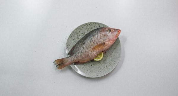 Pepare il pesce all'interno e all'esterno e inserire le fette di limone all'interno.