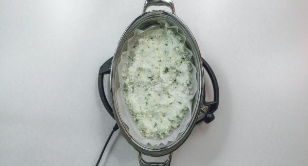 Versare ca. 1/3 della miscela di sale sulla carta da forno, adagiarvi il pesce e coprirlo completamente con il sale restante.
