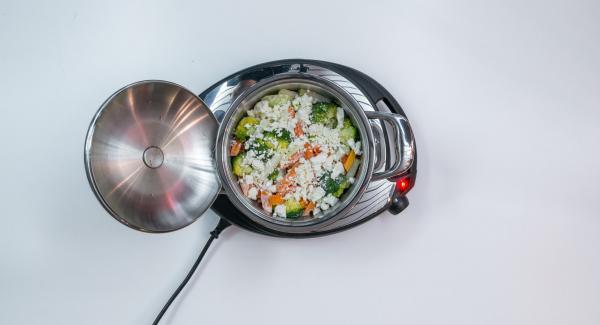 Tagliare a pezzetti la feta e cospargerla sulle verdure.