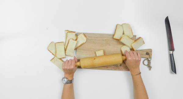Tagliare a metà le fette di toast e stenderle con il mattarello.