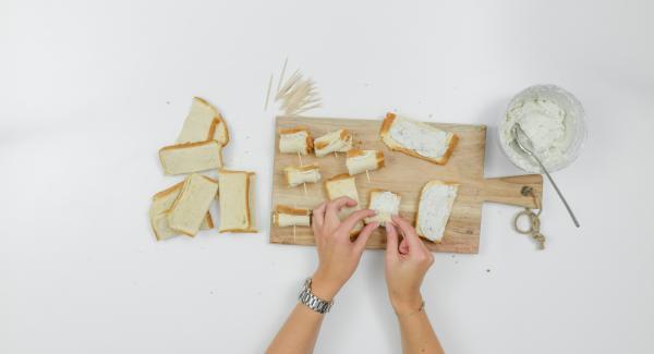Spalmare un po' di crema al formaggio su ciascuna striscia di pane, arrotolare e fissare con degli stuzzicadenti.