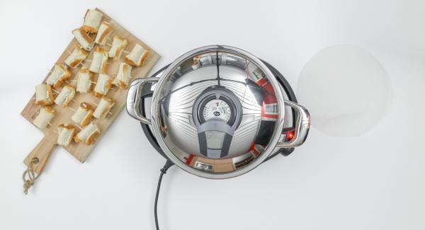 Al suono di Audiotherm, adagiare all'interno dell'Unità il disco di carta da forno e la metà dei rotolini.