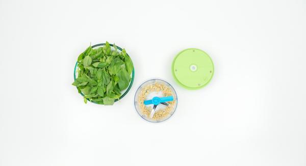 Pelare l'aglio, inserirlo nel Tritamix e tritarlo. Staccare le foglie del basilico.