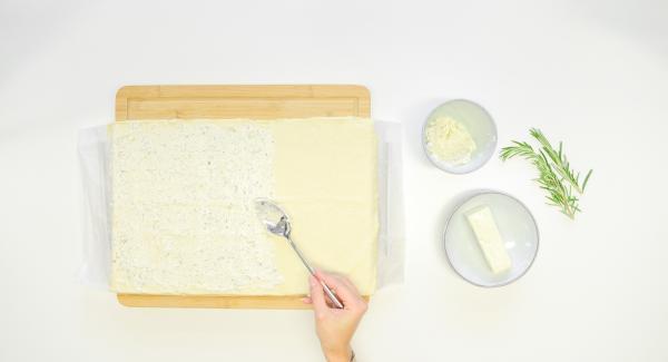 Spalmare il formaggio fresco alle erbe sulla pasta per la pizza.