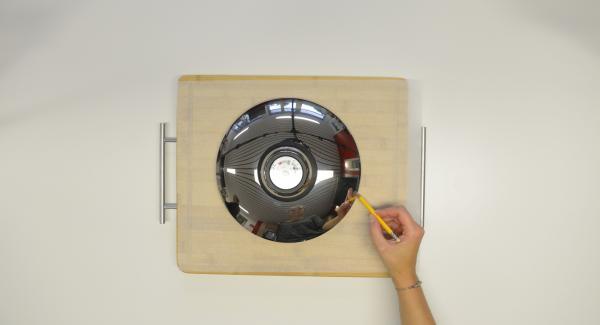 Con l'ausilio di un coperchio da 24 cm ritagliare un disco di carta da forno.