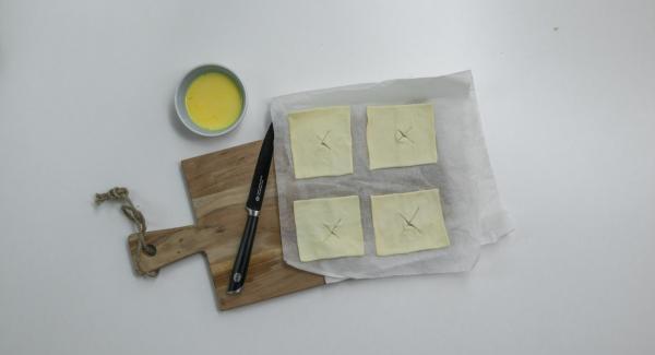 Incidere leggermente il quadrato di pasta sfoglia al centro facendo una croce o disegnando una piccola decorazione (es. cuore o stella) e spennellarla con il tuorlo d'uovo e il latte.