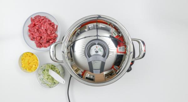 Al suono di Audiotherm, abbassare il calore e rosolare la carne di manzo. Aggiungere il trito di cipolla e i cubetti di peperone.