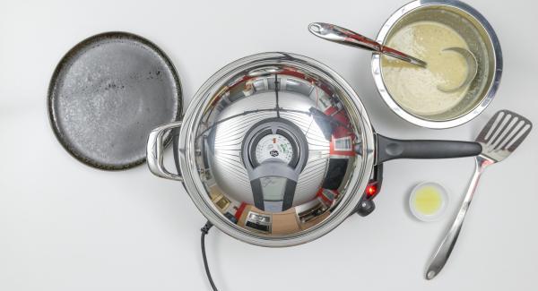 Al suono di Audiotherm, spegnere il fornello, aggiungere il burro fuso e adagiarvi un po' di impasto. Distribuire uniformemente l'impasto all'interno dell'Unità di cottura e coprire nuovamente con il coperchio. Impostare il fornello a calore basso.