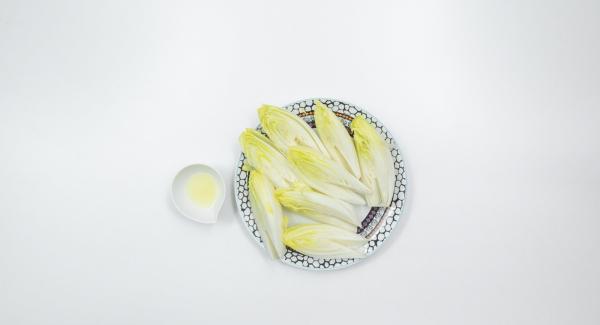 Lavare la cicoria, tagliarla a metà per il lungo ed eliminare la parte amara centrale. Sgocciolare leggermente e adagiare all'interno dell'Unità di cottura 24 cm 3,5 l e bagnare con succo di limone.