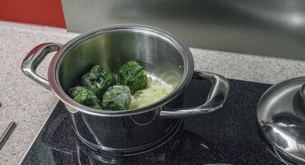 Posizionare all'interno dell'Unità di cottura 20 cm 3,0 l gli spinaci surgelati, 3 cucchiai di acqua e il trito di aglio e cipolla.