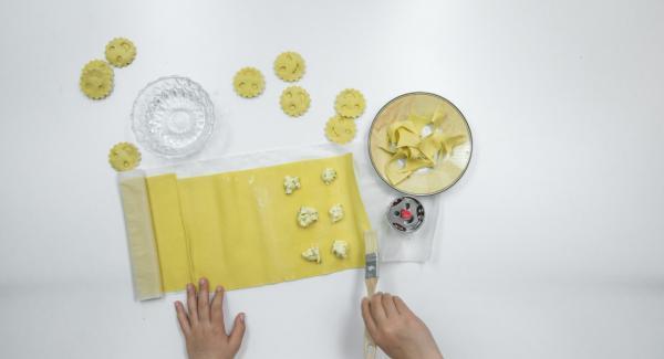 Stendere una sfoglia sottile di pasta e su una metà predisporre lo stampo dei ravioli. Mettere su ogni raviolo una pallina di ripieno e spennellare la pasta tutt'intorno con un po' di acqua.