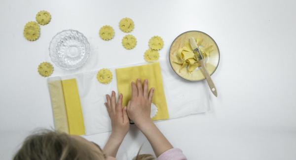 Coprire con cura con la seconda sfoglia di pasta e premere con gli stampini per inserire il ripieno. Tagliare i ravioli.