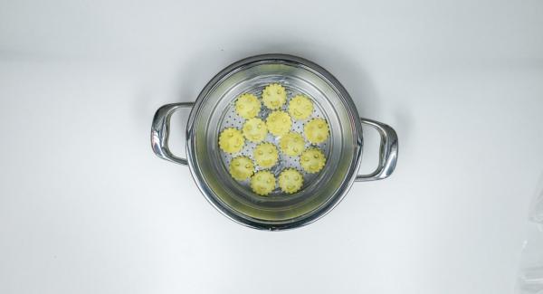 Con l'ausilio di un coperchio da 24 cm ricavare un disco di carta da forno e imburrare leggermente l'Inserto 2 in 1. Adagiarvi i ravioli e posizionare la carta da forno per poi posizionarvi un secondo strato di ravioli.