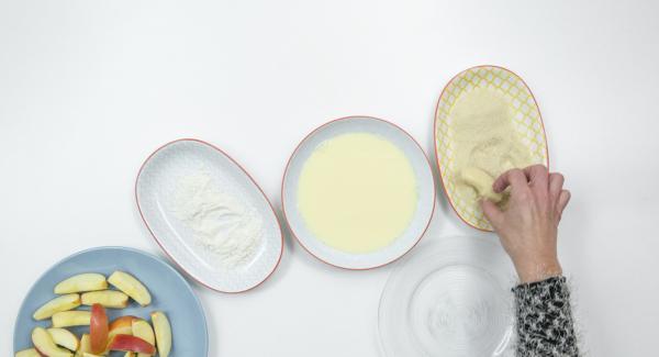 Impanare le fette di mela con farina, miscela di uovo e latte e poi pangrattato.