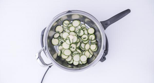 Adagiare le zucchine all'interno della Padella Arcobaleno e aggiungere lo spicchio d'aglio, l'origano e il rosmarino.