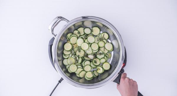 Al suono di Audiotherm, rimuovere il coperchio e far evaporare l'acqua. Aggiungere l'olio e far saltare le zucchine fino a doratura ultimata. Rimuovere l'aglio e servire.