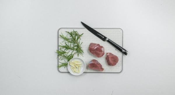 Pelare l'aglio e tagliarlo formando 12 striscioline. Dividere il rosmarino in 12 pezzetti. Tagliare in obliquo i medaglioni di maiale con un coltello sottile e affilato e inserire al loro interno un rametto di rosmarino e un pezzetto d'aglio.
