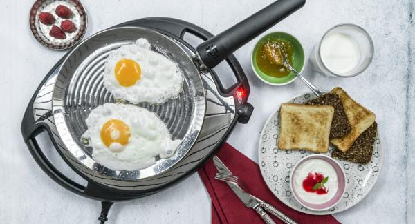 Posizionare le uova su oPan e cuocere finché non si raggiunge il livello di cottura desiderato. Condire con sale e pepe.