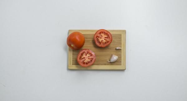 Tagliare a metà i pomodori e tagliare un'estremità dello spicchio d'aglio.