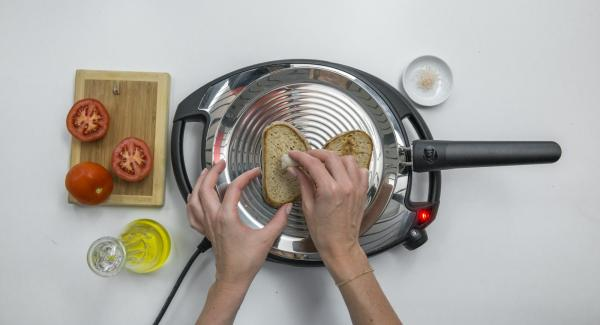 Abbassare Navigenio a livello 2, posizionare due fette di pane su oPan e cuocerle da un lato. Girarle e strofinarvi sopra l'aglio e il pomodoro.
