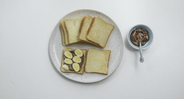 Spalmare la crema al cioccolato sulla metà delle fette di pancarrè e aggiungere dei pezzettini di banana. Coprire con le fette rimanenti.