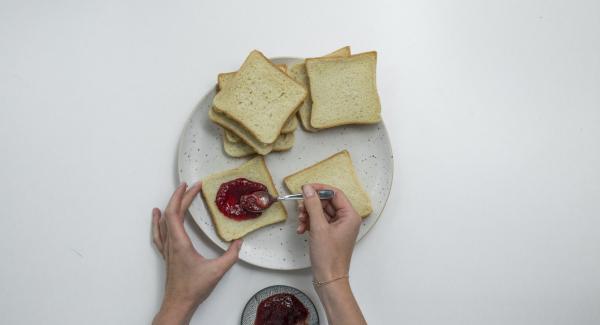 Spalmare la marmellata di prugne su metà delle fette di pancarrè e coprirle con l'altra metà.