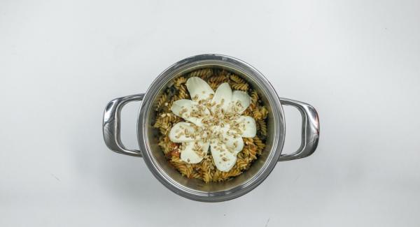 Tritare i pinoli, affettare la mozzarella e distribuirli sulla pasta all'interno dell'Unità di cottura. Posizionare l'Unità nel suo coperchio capovolto.
