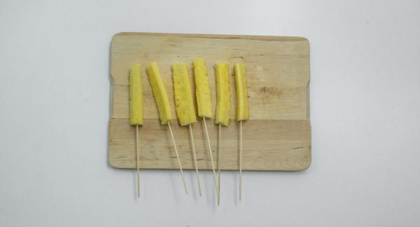 Tagliare l'ananas in 6 bastoncini e spolverizzarli con lo zucchero a velo. Infilare poi ogni bastoncino in uno spiedino di legno.