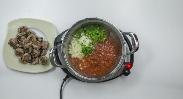 Rimuovere le polpette e mettere nell'Unità la cipolla, i pomodori in scatola, l'olio extravergine di oliva, l'origano, i cubetti di peperone e il prezzemolo rimanente.
