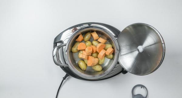 """Al suono di Audiotherm, aggiungere i pezzi di patata dolce bagnati e impostare nuovamente Navigenio in modalità """"A"""". Posizionare Audiotherm sulla finestra """"verdura"""" dopo aver impostato un tempo di cottura di 8 minuti."""